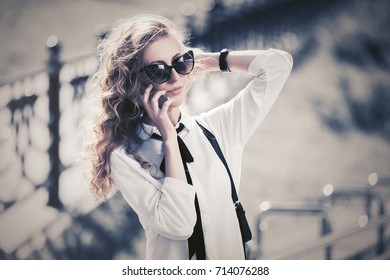 Blond business woman in sunglasses calling on smart phone in city street. Stylish fashion model in white blouse outdoor