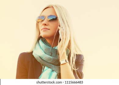 Blond business woman in sunglasses using cell phone walking outdoor Stylish fashion model wearing black blazer and turquoise scarf