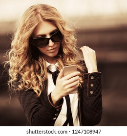 Blond business woman using smart phone on city street Stylish fashion model with long curly hairs wearing black jacket and sunglasses