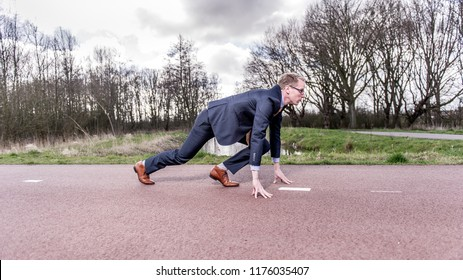 Blond businessman in suit is ready start running, sprinting on the road to succes