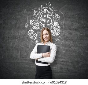 Blond businesswoman wearing a white shirt standing near blackboard and hugging her folder. There are shining dollar sign sketches on the chalkboard.
