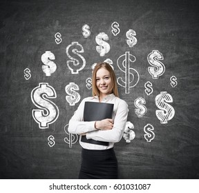 Blond businesswoman wearing a white shirt standing near blackboard and hugging her folder. There are dollar sign sketches on the chalkboard.