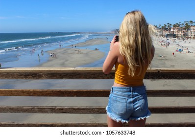 A blond California girl in cute shorts takes a picture of the ocean view from the Oceanside Pier on a sunny day