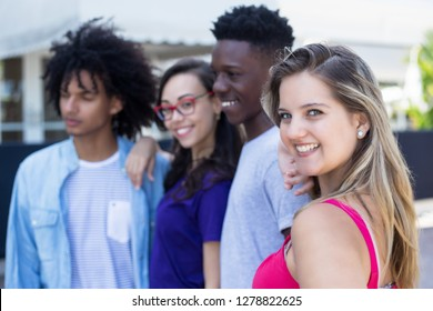 Blond caucasian woman with african and latin american young adults outdoor in the city