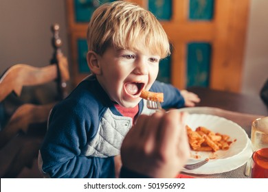 Blond child eats tomato pasta dish for lunch with family on Christmas Day
