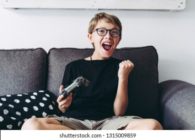 Blond child with eyeglasses legs crossed playing video games sitting on sofa  at home legs crossed Young student resting play on line with friends Domestic pastime challenge web exult happy winning