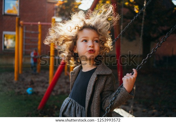 Blond curly girl swinging on a swing. The wind blows hair. Image with selective focus and toning. Grain effect.