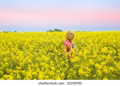 blond cute girl smiling and enjoying in a yellow field