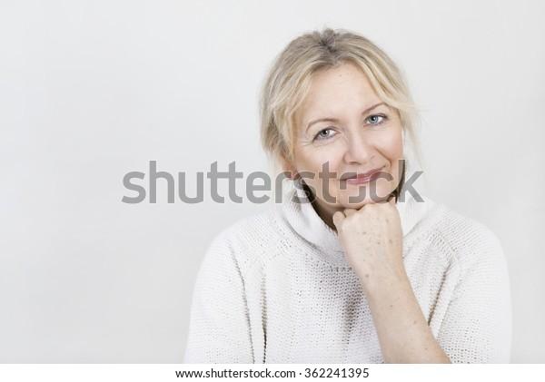 eine blonde ältere Frau, die auf die Kamera schaut