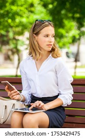 Blond elegant successful business girl in white shirt to go and touch pad during a break sitting outdoors in summer park on the background