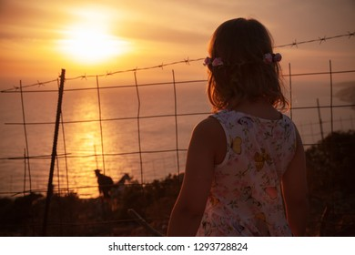Blond European little girl stands near barbed wire fence and looks on sunset over sea on horizon