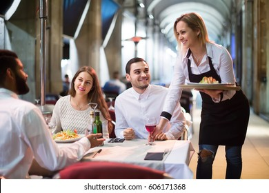 Blond european waitress bringing order at terrace table in summer day