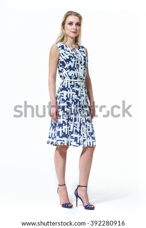 a5327ad86f9429 blond fashion model business executive woman in summer sleeveless blue  printed dress high heel shoes standing