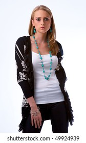 Blond fashion model in casual clothes with turquoise necklace and earrings on white background, with white blouse black jeans and flowered jacket