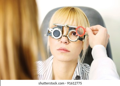 Blond female patient on medical attendance at the optometrist, wearing trial frame for eye testing