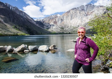 Blond female poses by Convict Lake in the springtime, located off of US-395, near Mammoth Lakes California in the eastern Sierra Nevada mountains, Inyo National Forest.
