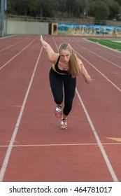 Blond female runner in black tights at full speed.
