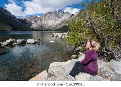 Blond female sits alone by Convict Lake in the springtime, located off of US-395, near Mammoth Lakes California in the eastern Sierra Nevada mountains, Inyo National Forest.