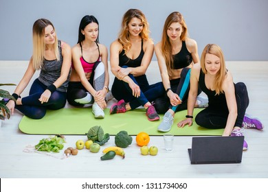 Blond female trainer consulting group of four sports women about healthy food, eating nutritional concept. clean fruits, water glass. Nutritionist conduct training fitness sitis on floor with laptop.