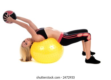 Blond fitness trainer demonstrating a body ball and medicine ball yoga technique