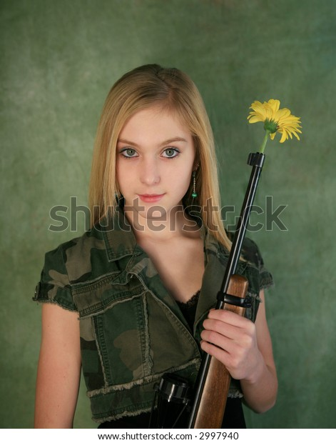 Blond girl with big green eyes holding rifle with daisy in the end on green background