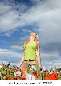 Blond girl in blooming poppy field