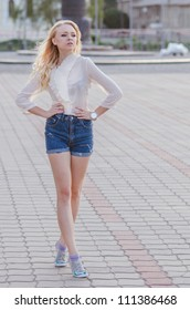 Blond girl in a blue jeans shorts walking down the street