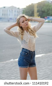 Blond girl in a  blue jeans shorts and white blouse  posing on the street