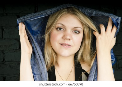 Blond girl with blue silk scarf looking at camera, studio shot