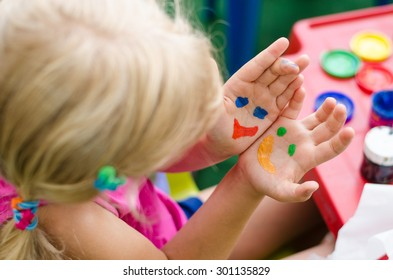 blond girl with colorful painted hands