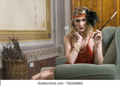 Blond girl with curly hair posing in 1920s vintage clothes inside a villa's hall