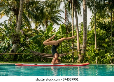 Blond girl doing a SUP yoga headstand in a pool in a Ceylon Jungle.