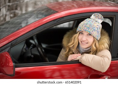 Blond girl driving a red car in winter. A woman is smiling in a hat.