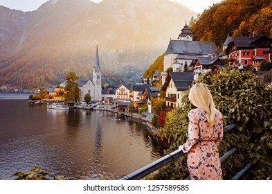 Blond girl enjoying at the wonderful colorful sunset and autumn trees. Scenic view of famous Hallstatt mountain village with Hallstatt lake at autumnh. Travel concept. Travel happy emotions. Lifestyle