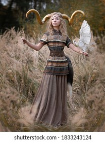 Blond girl with golden horns and an owl with spread wings on her hand