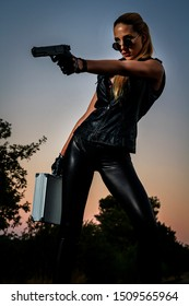 Blond girl in handcuffs on the background of an abandoned railway. Sexy woman in black leather clothes with gun at night. Criminal gangsta woman escape from mafia. Spy with weapon.