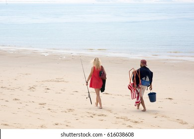 Blond girl and her boy friend on the beach to go fishing