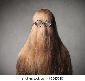 Blond girl with her hair on her face wearing eyeglasses