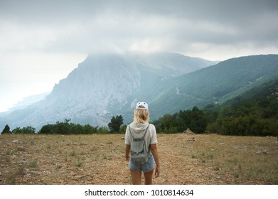 Blond girl hiking against misty mountains at cloudy weather. Back view, focus on landscape.