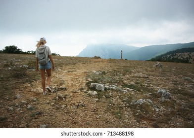 Blond girl hiking against misty mountains at cloudy weather. Back view.