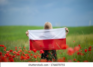 Blond girl holding flag of Poland in the poppy field. Back  view. Polish Flag Day. Independence Day. Travel and learn polish language concept.
