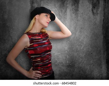 A blond girl is holding her black hat and looking to the side. The wall behind her is textured and black. Use it for a nightclub or culture concept.