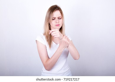 Blond girl holding a sick hand, arthrosis