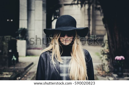 57a1b32c8c8 Blond girl incognito at cemetery hiding her face under a black hat.  Selective focus on