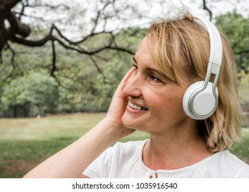 blond girl listening to music in nature, woman listening music radio with wireless headphones on mobile cheerful in park, Happy life concept