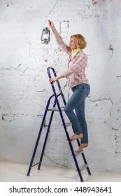 Blond girl with lit lantern standing on stepladder