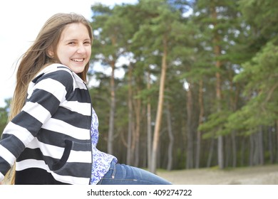 Blond girl with long hair is sitting and smiling. The pines are on the background.