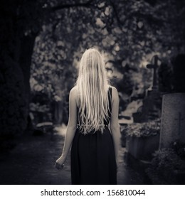 Blond girl with long hair walking alone in the dark at cemetery