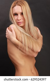 Blond Girl with long healthy hair and natural skin on dark background.