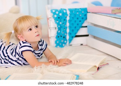 blond girl lying on the floor with books next to teddy bear